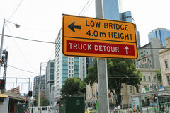 A yellow and black 'Low Bridge, 4m Height' and 'Truck Detour' sign near the Flinders Street rail bridge royalty free stock photos