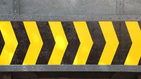 Yellow and black arrow sign on steel plate Stock Image
