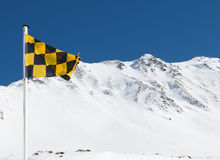 Yellow and black avalanche risk warning flag flying in the mount. Ains Stock Photography