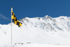Yellow and black avalanche risk warning flag flying in the mount. Ains Royalty Free Stock Image