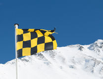 Yellow and black avalanche risk warning flag flying in the mount. Ains stock image