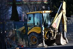 Yellow and Black Backhoe Near the Wire Fence Stock Photos