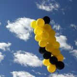 Yellow Black Balloons. Yellow and black ballons with a blue cloudy sky Royalty Free Stock Images