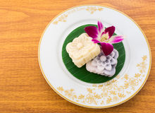 Yellow and Black Carved Mochi Cake on Thai Banana Leaf in a Whit. Yellow and Black Carved Mochi Cake on a Thai Banana Leaf in a White Gold Pattern Plate Stock Image