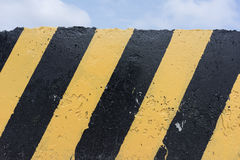 Yellow and black concrete barrier stock image