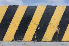 Yellow and black concrete barrier. Yellow and black stripes on the concrete surface Royalty Free Stock Photography