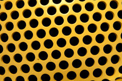 Yellow and Black Holes. Black evenly spaced holes on yellow metal stock photography