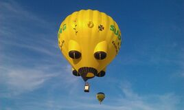 Yellow and Black Hot Air Balloons on Mid Air Under White Clouds Blue Sky during Daytime Stock Photography