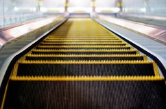 Indoor escalator with view from the top. Yellow and black indoor escalator with view from the top going down Royalty Free Stock Images
