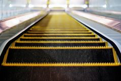 Indoor escalator with view from the top. Yellow and black indoor escalator with view from the top going down Stock Image