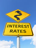 Yellow and black Interest Rates Rising road sign in a blue sky. Yellow and black Interest Rates Rising road sign with arrow in a blue sky royalty free stock photos