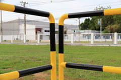 Yellow and black iron fence around small groundwater pump Stock Images
