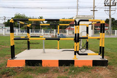 Yellow and black iron fence around small groundwater pump Stock Photography