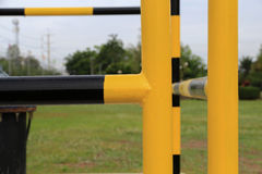 Yellow and black iron fence around small groundwater pump Stock Photo
