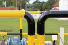 Yellow and black iron fence around small groundwater pump Stock Image