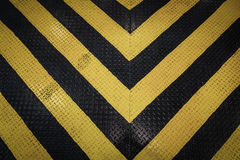 Yellow and black marking warning sign, grunge background Royalty Free Stock Photos