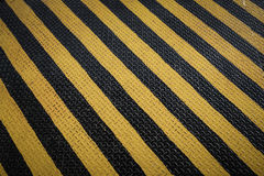 Yellow and black marking warning sign, grunge background Stock Photography