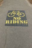 Yellow and black painted No Bike Riding sign on asphalt pedestrian footpath stock images