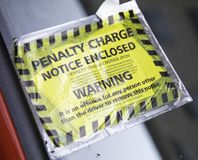 A yellow and black parking penaty charge notice attached to a pa. Rked car Liverpool May 2018 Royalty Free Stock Photography