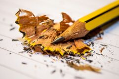 Yellow Black Pencil Sharpened Above the White Paper in Macro Photography Stock Photography