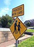 Yellow and black proceed with care sign and aged care facility Stock Photography