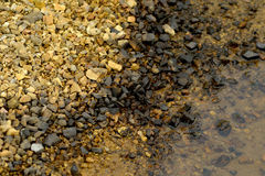 Yellow Black rocks and water Royalty Free Stock Image