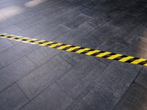Yellow Black Safety Warning Tape on Tiled Floor Covering Electrical Cable Underneath. High Angle View of Yellow Black Safety Warning Tape on Tiled Floor Covering royalty free stock photos