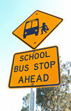 Yellow and black school bus stop ahead sign and blue sky. Yellow and black school bus stop ahead road safety sign with blue sky and trees Royalty Free Stock Image