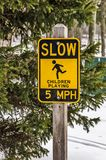 Drive Slow and Watch for Children Playing. Yellow and black sign to warn drivers that children might be playing in the road.  Slow down Royalty Free Stock Photo