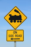 Yellow and black trains on side road sign in a cloudless blue sky Stock Photography