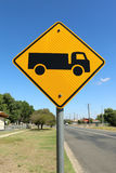 Yellow and black Trucks Entering On Side Road sign in blue sky Royalty Free Stock Image