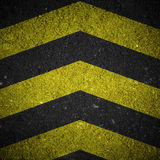 Yellow and black warning sign on asphalt texture Royalty Free Stock Images