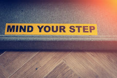 Yellow and black warning sign on stairs stating Stock Photography
