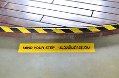 Yellow and black warning sign on step stating Stock Photo