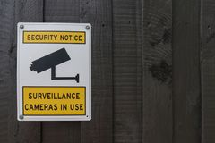 Yellow, black and white Security Notice, Surveillance Cameras In Use warning sign on a painted wooden fence stock photos