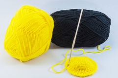 Yellow and black yarn balls with crochet hook Stock Images