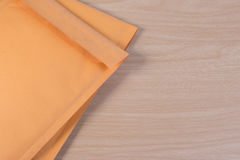 Yellow blank envelope with transparent bubble wrap or packaging shockproof on wooden table. Stock Image