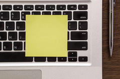 Yellow blank paper note on laptop keyboard Royalty Free Stock Images