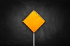 Yellow blank road sign on black wall.  Royalty Free Stock Photography