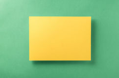 Yellow blank sheet of paper light green background Royalty Free Stock Images
