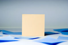 Yellow blank sheet for records amid blue sheets lying Royalty Free Stock Photos