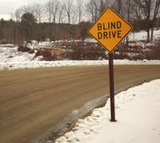 Yellow blind drive sign on a winding dirt road Royalty Free Stock Photo