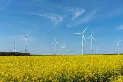 Yellow blooming oilseed and some wind energy plants. Seen in rural Germany stock images