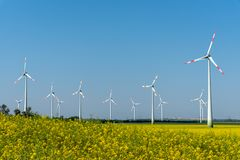 Yellow blossoming oilseed and some wind energy plants. Seen in rural Germany stock photography