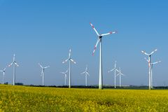 Yellow blossoming rapeseed and some wind energy plants. Seen in rural Germany royalty free stock images