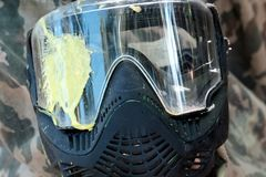 Paintball. Yellow blot on the glass of the protective mask on a camouflage background. The concept of defeat and loss. Sports. Yellow blot on the glass of the stock image