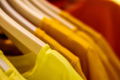 Yellow blouse on a hanger in the closet hanging Stock Image