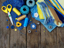 Yellow and blue accessories for needlework on brown wooden background. Knitting, embroidery, sewing. Small business. Income from h Royalty Free Stock Photos