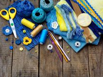Yellow and blue accessories for needlework on brown wooden background. Knitting, embroidery, sewing. Small business. Income from h Royalty Free Stock Image