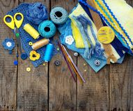 Yellow and blue accessories for needlework on brown wooden background. Knitting, embroidery, sewing. Small business. Income from h Stock Image